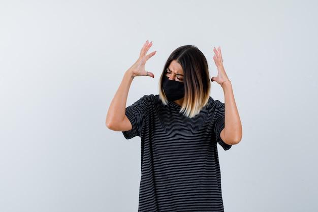 Senhora levantando as mãos de forma agressiva em vestido preto, máscara médica e parecendo irritada. vista frontal.