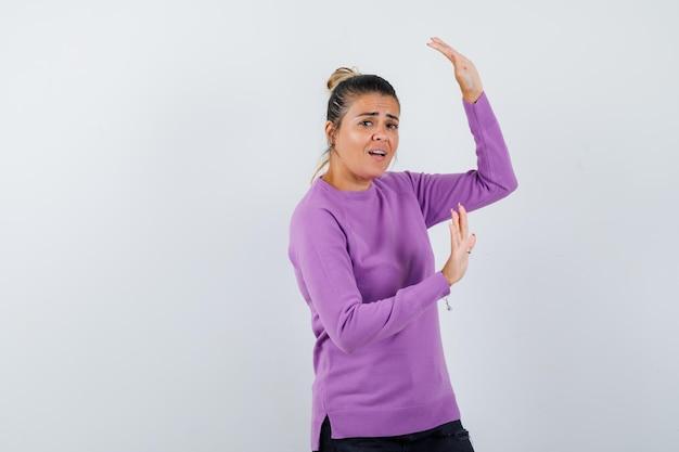 Senhora levantando as mãos para se defender com uma blusa de lã e parecendo animada