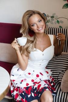 Senhora lindo vestido de verão, bebendo café no café.