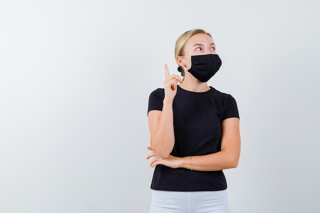 Senhora loira apontando para cima com camiseta preta, máscara preta e parecendo pensativa