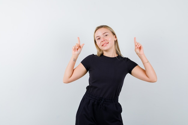 Senhora loira apontando para cima em um vestido preto e parecendo feliz, vista frontal.