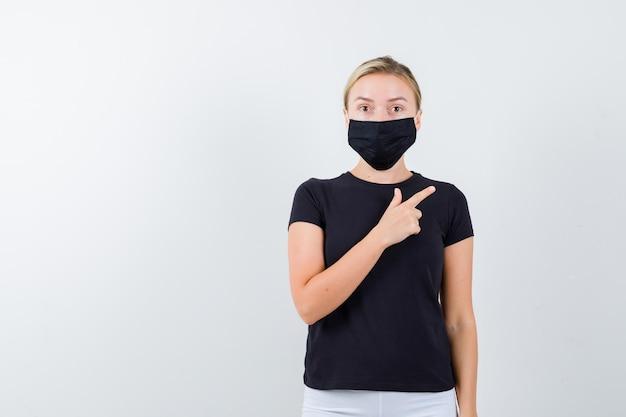 Senhora loira apontando para o canto superior direito em camiseta preta isolada