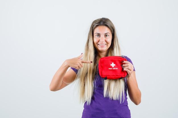 Senhora loira apontando para o kit de primeiros socorros em t-shirt violeta e olhando alegre, vista frontal.