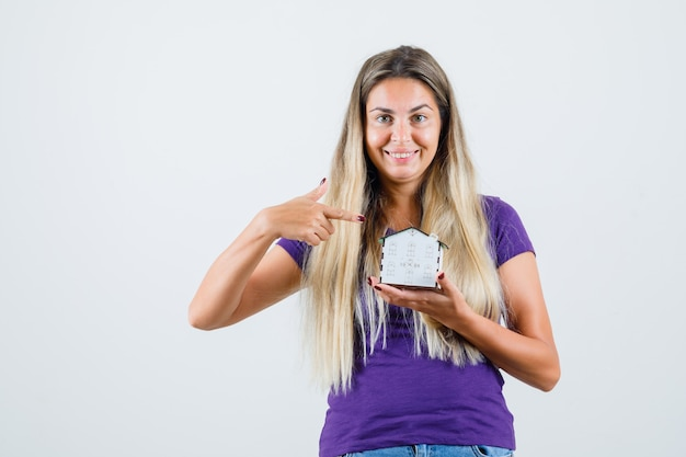 Senhora loira apontando para o modelo de casa em t-shirt violeta, jeans e olhando alegre, vista frontal.