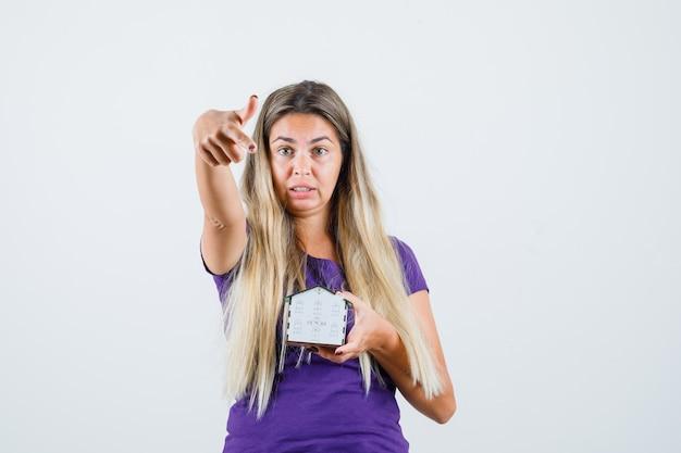 Senhora loira apontando para o modelo de casa em t-shirt violeta, vista frontal.