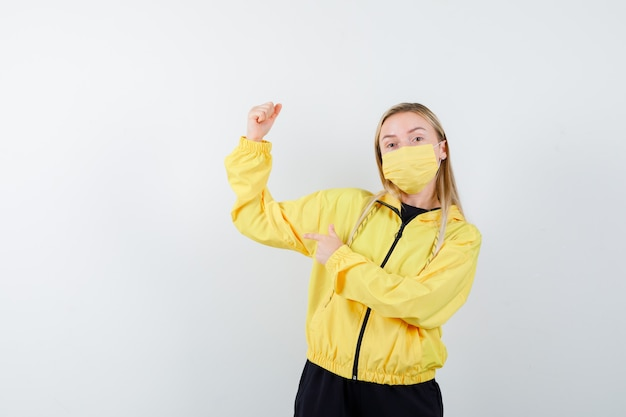 Senhora loira, apontando para os músculos do braço em agasalho, máscara e parecendo orgulhosa. vista frontal.