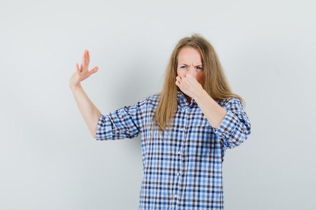 Senhora loira beliscando o nariz devido ao mau cheiro na camisa e parecendo enojada,