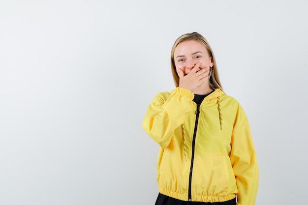 Senhora loira com agasalho, mantendo a mão na boca e parecendo alegre, vista frontal.