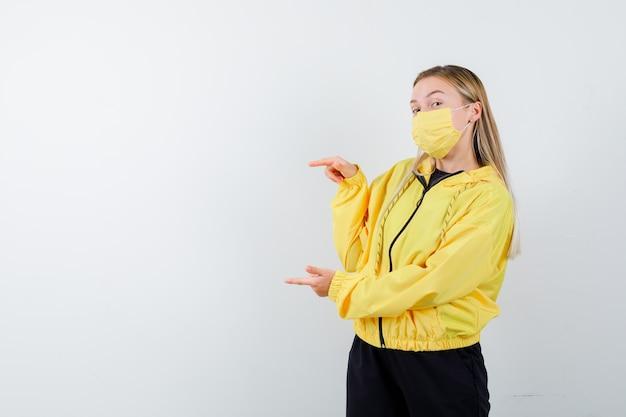 Senhora loira com agasalho, máscara apontando para a esquerda e parecendo confiante, vista frontal.