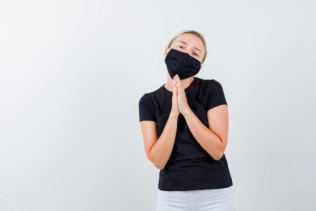 Senhora loira com camiseta preta, máscara preta mantendo as mãos em gesto de oração