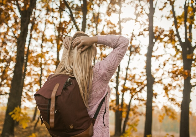 Senhora loira com mochila virou-se para enfrentar o sol