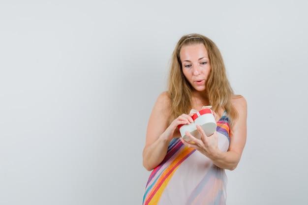 Senhora loira com vestido de verão segurando uma caixa de presente e parecendo curiosa