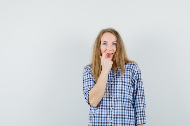 Senhora loira de camisa roendo a unha e parecendo envergonhada,