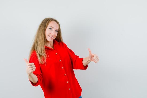 Senhora loira de camisa vermelha mostrando dois polegares para cima e parecendo alegre,
