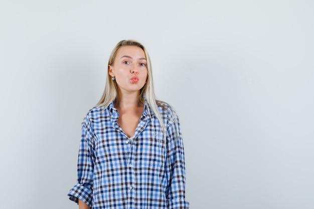 Senhora loira de camisa xadrez com beicinho nos lábios e aparência atraente
