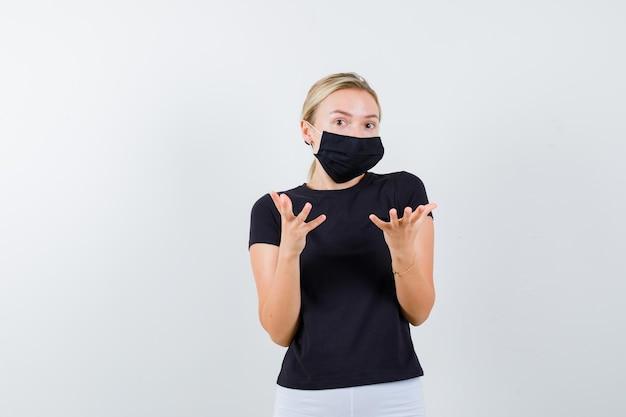 Senhora loira de camiseta preta, máscara preta levantando as mãos em um gesto perplexo
