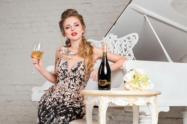 Senhora loira elegante com um copo de vinho sentado perto de um piano de cauda branco em um interior clássico de luxo. mulher jovem com corpo perfeito e rosto bonito maquiado em vestido de noite comemorando, bebendo álcool