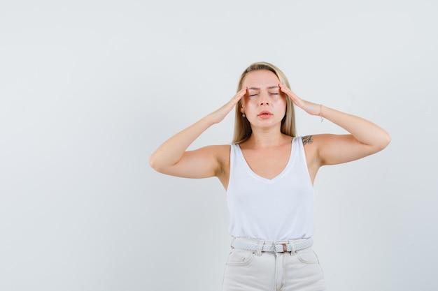 Senhora loira esfregando as têmporas em camiseta, calças e parecendo exausta, vista frontal.