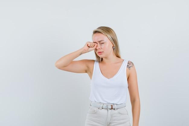 Senhora loira esfregando os olhos enquanto chorava em camiseta, calças e parecendo ofendida. vista frontal.