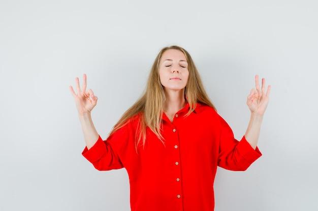 Senhora loira fazendo meditação com os olhos fechados, de camisa vermelha e parecendo relaxado.