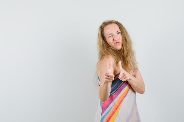 Senhora loira fazendo sinal de pistola com o dedo e piscando em um vestido de verão