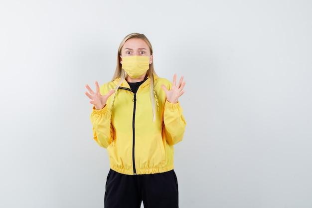 Senhora loira levantando as mãos com agasalho, máscara e parecendo assustada. vista frontal.