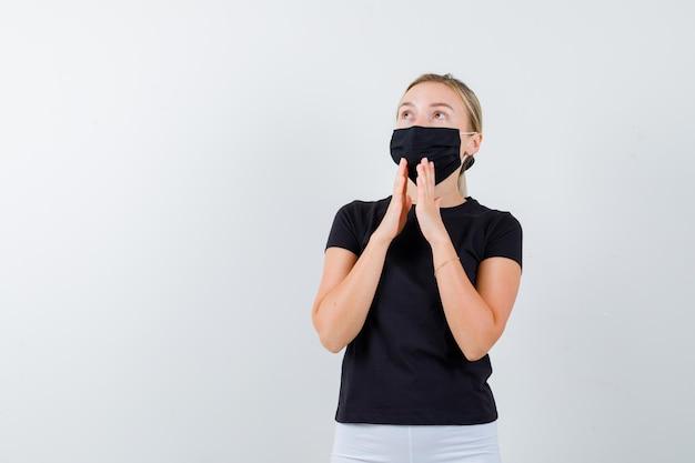 Senhora loira mantendo as mãos em gesto de oração em camiseta preta isolada