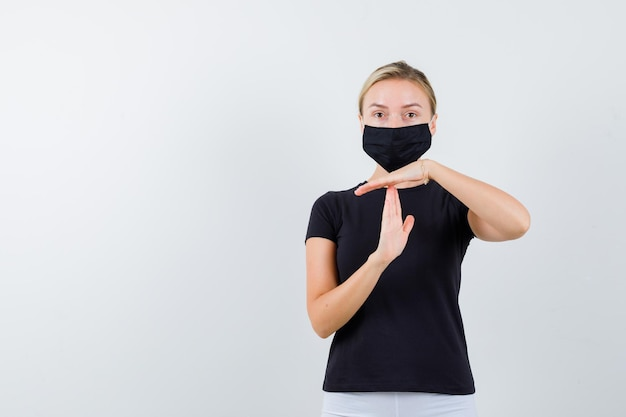 Senhora loira mostrando gesto de intervalo em uma camiseta preta, máscara preta e parecendo confiante