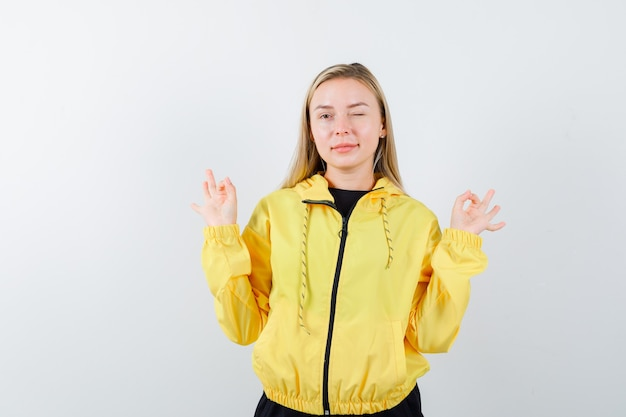 Senhora loira mostrando gesto de ioga, piscando os olhos com agasalho e parecendo confiante. vista frontal.