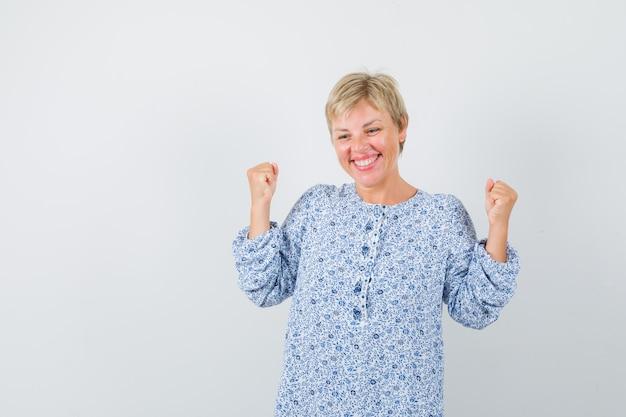 Senhora loira mostrando gesto de vencedor em blusa estampada e parecendo alegre. vista frontal.