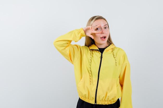 Senhora loira mostrando o sinal de v no olho com agasalho e parecendo espantada. vista frontal.