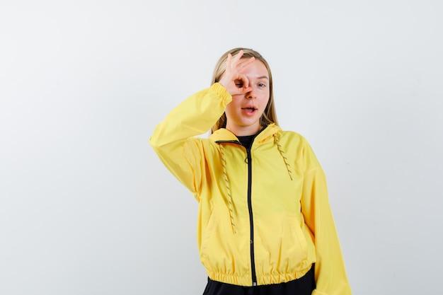 Senhora loira mostrando sinal ok no olho com agasalho e olhando espantada, vista frontal.