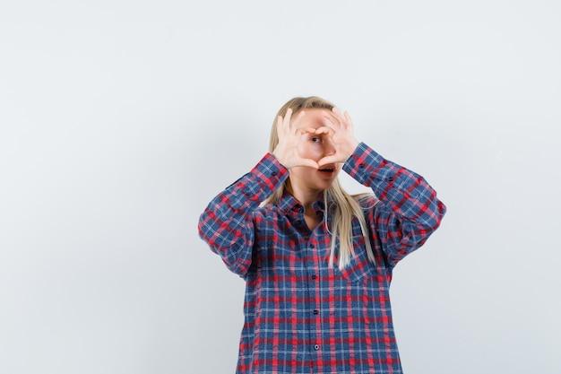 Senhora loira mostrando um gesto de coração na camisa casual e olhando feliz, vista frontal.