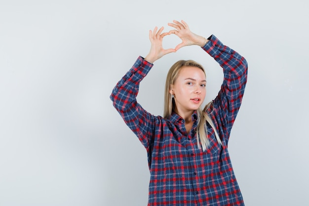 Senhora loira na camisa casual, mostrando o gesto do coração e olhando feliz, vista frontal.