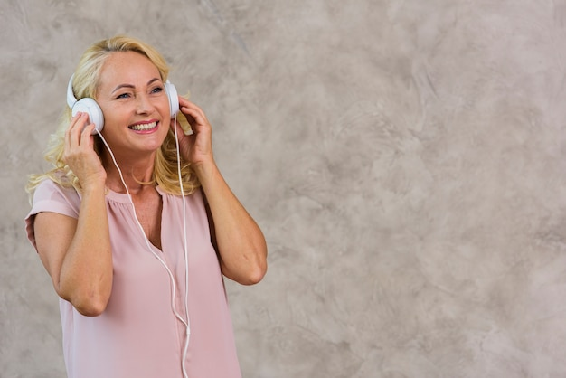Senhora loira ouvindo música no fone de ouvido