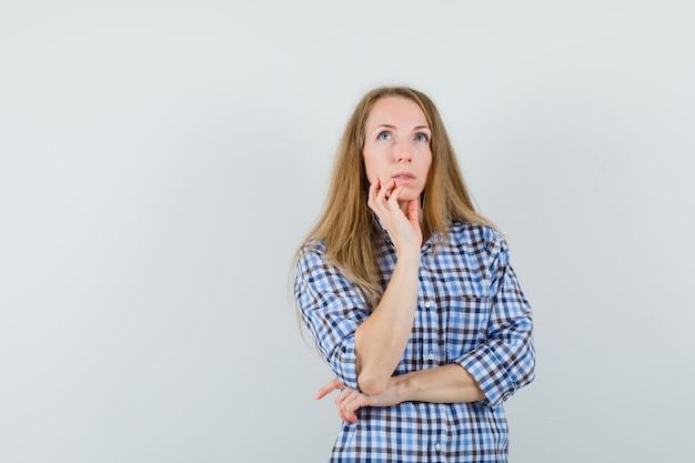 Senhora loira segurando o queixo na camisa e parecendo pensativa,
