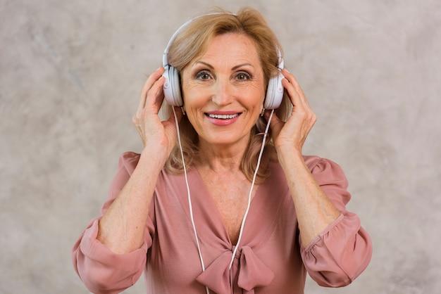 Senhora loira sorridente, ouvindo música no conjunto de fones de ouvido