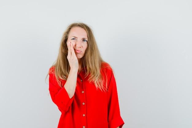 Senhora loira tendo dor de dente na camisa vermelha e parecendo desconfortável.