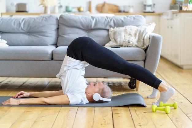 Senhora madura positiva fazendo exercícios de força mantendo-se em boa forma, excelente preparo físico na aposentadoria