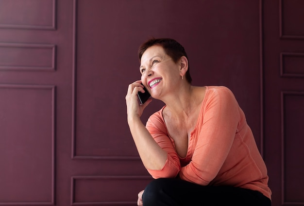 Senhora madura sorridente, falando ao telefone