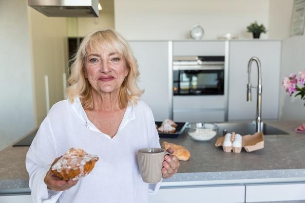 Senhora madura sorridente segurando a xícara de café