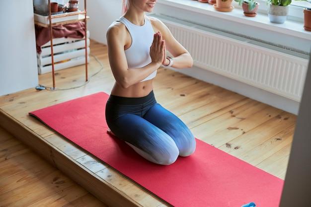Senhora magra de top e leggings sentada de mãos dadas em namaste durante o treinamento de ioga na varanda