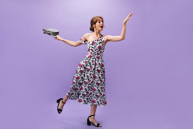 Senhora magra em lindo vestido salta com bolsa no fundo roxo. mulher jovem e encantadora com roupas florais longas detém bolsa cinza.