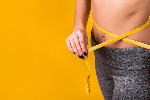 Senhora magro, medindo a cintura por fita