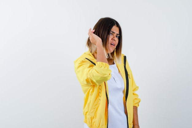 Senhora mantendo a mão atrás da orelha em uma camiseta, jaqueta e parecendo confusa. vista frontal.