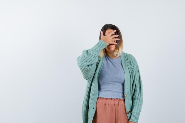 Senhora mantendo a mão nos olhos em roupas casuais e parecendo assustada. vista frontal.