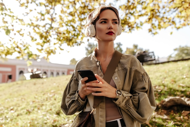 Senhora maravilhosa com cabelo curto em fones de ouvido brancos e jaqueta verde-oliva, olhando para longe ao ar livre. mulher com bolsa segura o telefone do lado de fora.