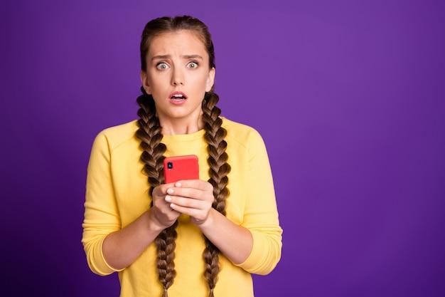 Senhora milenar segurando um telefone lendo novos comentários de notícias falsas, olhos de boca aberta cheios de medo, vestir um casaco amarelo casual isolado na parede roxa