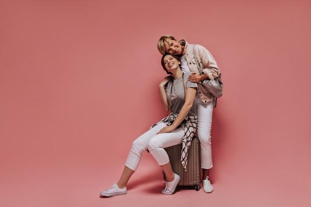 Senhora moderna, com cabelo morena em camisa xadrez e calça branca, sentada na mala e posando com uma mulher sorridente com roupa leve em pano de fundo rosa.