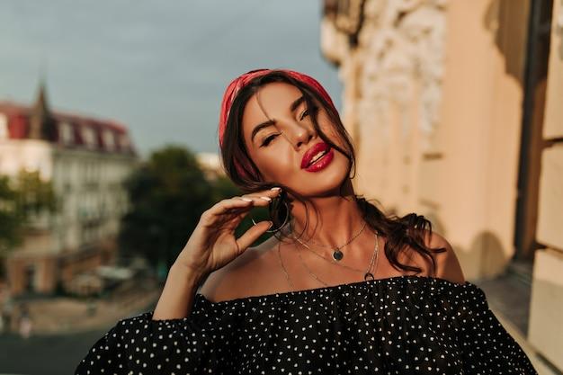 Senhora moderna e brilhante com bela maquiagem, bandana rosa e manicure branca em uma camisa preta de bolinhas, olhando para a câmera na varanda.